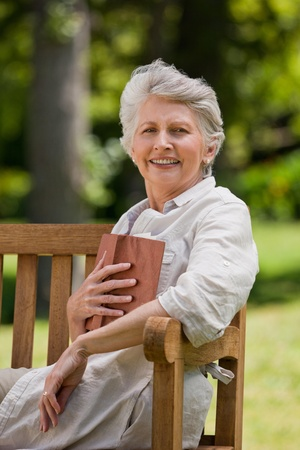 Retired woman reading a book on the  bench photo