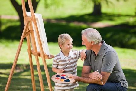 grandfather: Abuelo y su nieto de pintura en el jard�n Foto de archivo