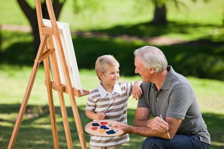 only seniors: Grandfather and his grandson painting in the garden Stock Photo