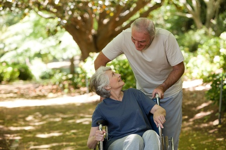 wheelchair woman: Senior couple in the woods