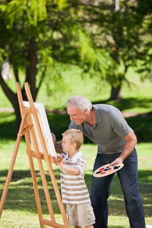 Grandfather and his grandson painting in the garden Stock Photo