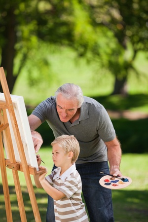 Grandfather and his grandson painting in the garden photo
