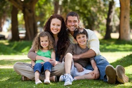 Familia feliz sentada en el jard�n Foto de archivo - 10219540