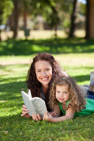 Woman with her daughter reading a book photo