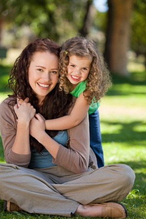 Woman hugging her daughter in the park photo