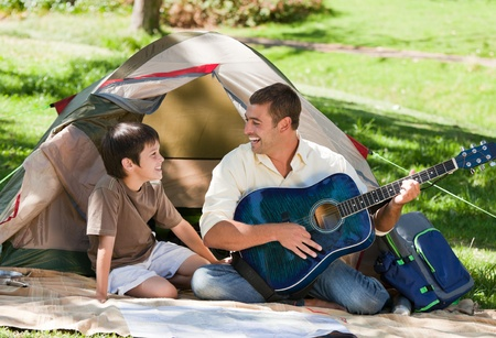 Father playing guitar with his son photo