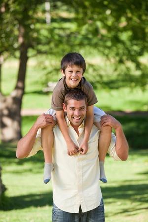 happy retirement: Handsome man giving son a piggyback