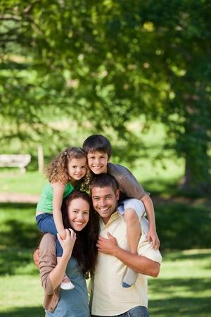 famiglia in giardino: Genitori dando bambini un piggyback