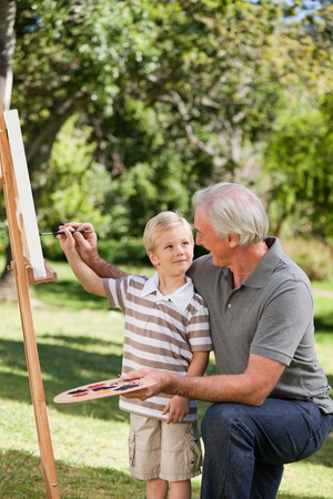 Happy Grandfather and his grandson painting in the garden Stock Photo - 10219462