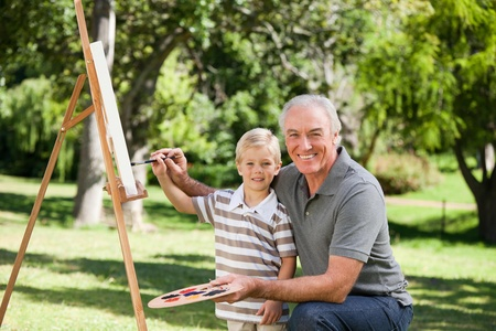 Happy Grandfather and his grandson painting in the garden photo