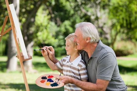 only seniors: Happy Grandfather and his grandson painting in the garden