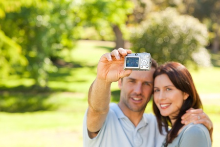 Couple taking a photo of themselves in the park photo