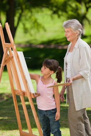 Grandmother and her granddaughter painting in the garden photo