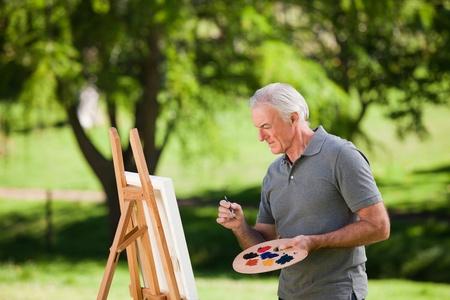 Senior man painting in the garden Stock Photo