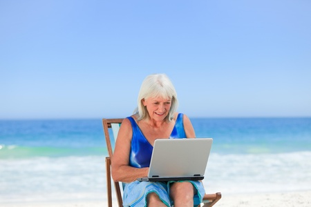 Woman working on her laptop on the beach Stock Photo - 10207535
