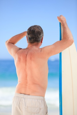 Mature man with his surfboard photo