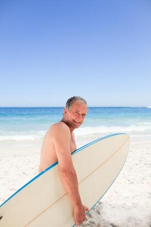 jubilados: Hombre retirado con su tabla de surf Foto de archivo