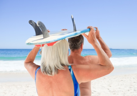 Senior couple with their surfboard photo