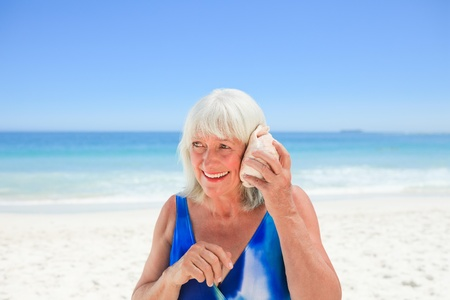 Woman listening to her shell photo