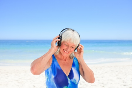 Senior woman listening to some music beside the sea Stock Photo - 10207497