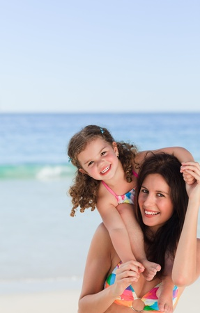 Mother playing with her daughter on the beach photo