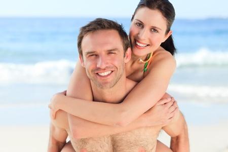 Man having wife a piggyback on the beach photo
