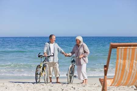 Elderly couple with their bikes on the beach photo
