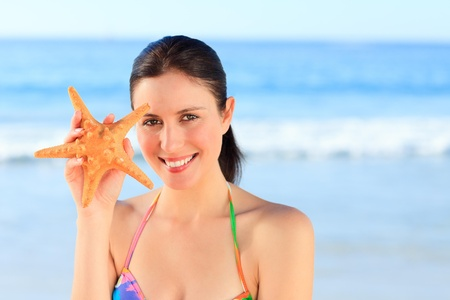 Pretty woman with a starfish Stock Photo - 10207538