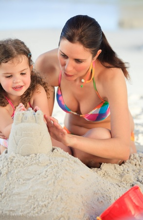 Daughter with her mother making a sand castle photo