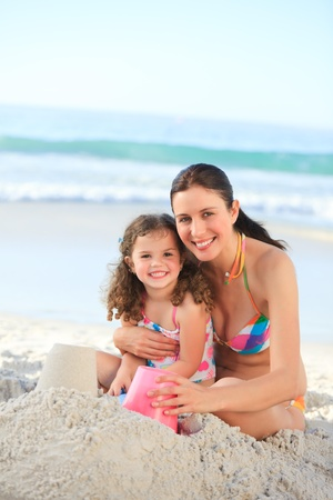 sand castle: Daughter with her mother making a sand castle Stock Photo