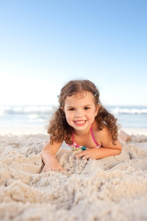 Little girl lying down on the beach Stock Photo