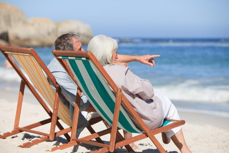 Retired couple sitting on deck chairs photo