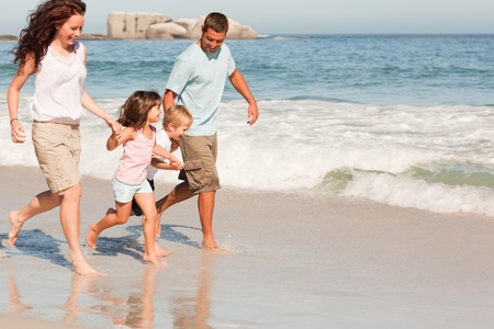 lovers holding hands: Family running on the beach Stock Photo