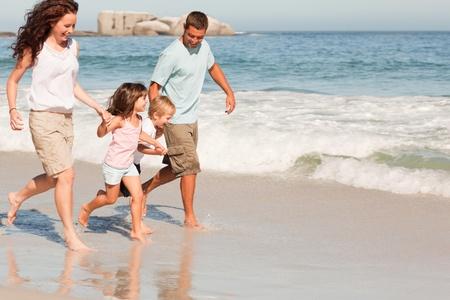 beach model: Family running on the beach Stock Photo