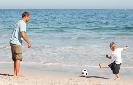 dad son: Father playing football with his son Stock Photo