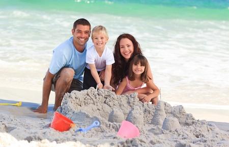 familia jugando: Familia radiante en la playa Foto de archivo