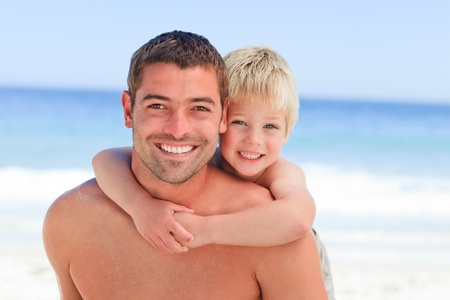 Smiling father having son a piggyback at the beach photo