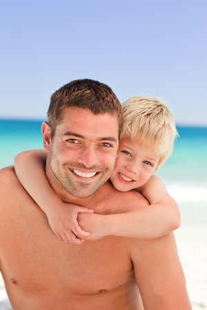 Smiling father having son a piggyback at the beach Stock Photo - 10216167