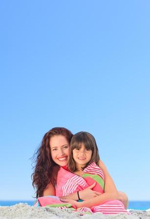 familia animada: Sonriente mujer con su hija en una toalla