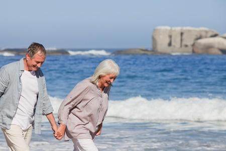 Elderly couple walking on the beach photo