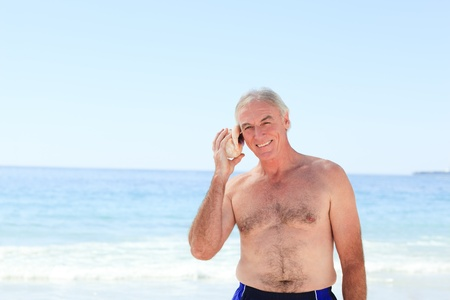 Senior man listening to his shell Stock Photo - 10214250