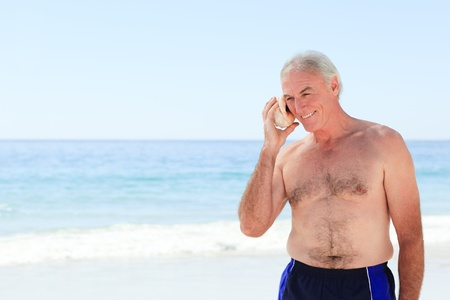 Senior man listening to his shell Stock Photo - 10214256