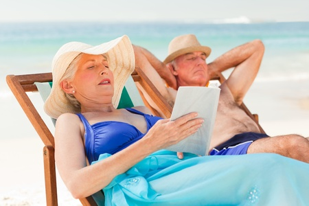 Woman reading a book while her husband is sleeping at the beach  photo