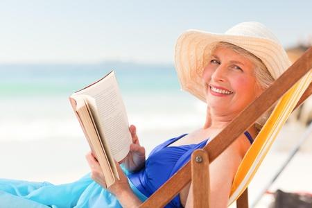 mujeres sentadas: Anciana leyendo un libro en la playa Foto de archivo
