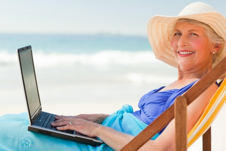 Happy woman working on her laptop at the beach Stock Photo - 10216072