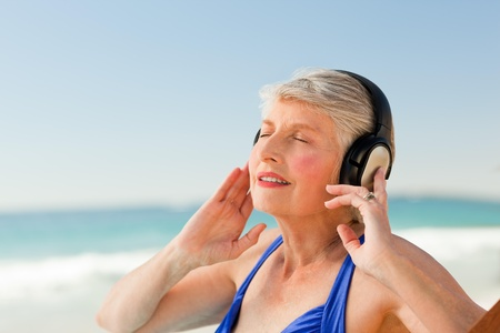 Senior woman listening to music at the beach photo