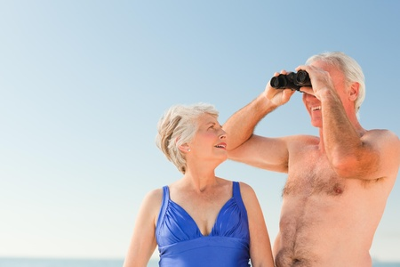 Elderly couple bird watching at the beach photo