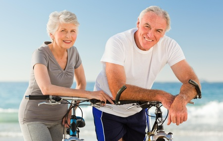 Retired couple with their bikes on the beach photo