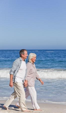 seniors walking: Elderly couple walking on the beach