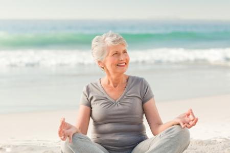Senior woman practicing yoga on the beach Stock Photo - 10213960